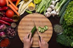 Människan räcker den bitande gurkan och variation av grönsaker och kryddor omkring Royaltyfri Foto