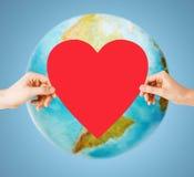 Människan räcker hållande röd hjärta över jordjordklotet royaltyfri fotografi