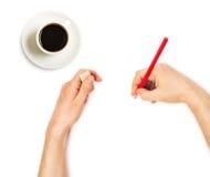 Människan räcker med ritar och raderar gummi och kuper av kaffe Arkivbild