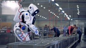 Människan som roboten arbetar på en fabrik, genom att använda ett specialt hjälpmedel arkivfilmer