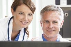 Männlich-weibliche Krankenhaus-Doktoren, die Computer verwenden Stockfoto