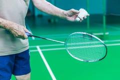 Männliche ältere Hand des einzelnen Spielers des Badminton hält weißen Shuttlehahn, servierfertige Vorhand mit Schläger auf grüne stockbild