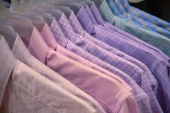 Männliche Abnutzung auf Plastikaufhänger Offizielle Abnutzung für Männer im Kaufhaus Pastellhemden auf hängt für Verkauf im Gesch lizenzfreies stockfoto