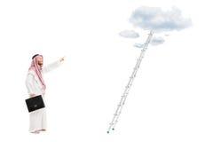Männliche arabische Person mit dem Aktenkoffer, der vor eine Leiter wi steht Stockbild