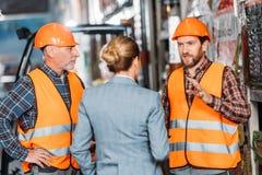 männliche Arbeitskräfte in den Sicherheitswesten und Sturzhelme, die mit Inspektor sprechen lizenzfreie stockfotos