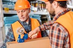 männliche Arbeitskräfte in den Sicherheitswesten und Sturzhelme, die Pappschachtel verpacken lizenzfreies stockfoto