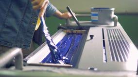 Männliche Arbeitskraft benutzt eine Bürste zu sogar einer Schicht einer blauen Farbe in einem speziellen Abschnitt einer Maschine stock footage