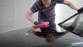 Männliche Arbeitskraft der Rothaarigen verarbeitet die Oberfläche des Autos durch Poliermaschine in einem Autoservice und bedeckt stock footage