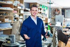 Männliche Arbeitskraft, die Bohrgerät für Arbeit an der Werkstatt verwendet Stockfotos