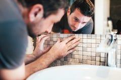 männliche Arbeitskraft, die keramische Mosaikfliesen auf Badezimmerwände installiert Lizenzfreie Stockbilder