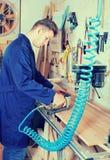 Männliche Arbeitskraft, die mit Fräser an der Werkstatt arbeitet Stockbilder