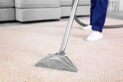 Männliche Arbeitskraft, die Schmutz vom Teppich entfernt stockfoto