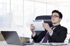 Männliche Arbeitskraft, die Tablette im Büroraum verwendet Stockfoto