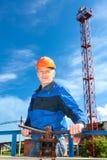Männliche Arbeitskraft in einer Arbeitsuniform mit Rohrventil Stockfotografie