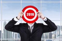 Männliche Arbeitskraft hält Dartscheibe mit Nr. 2016 Stockfoto
