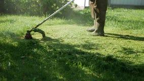 Männliche Arbeitskraft mit TreibstoffRasenmähertrimmer mit dem Motor, der Gras an einem sonnigen Sommertag schneidet Schnitt des  stock footage