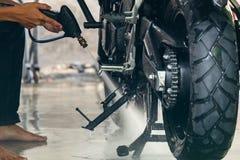 Männliche Arbeitskraft-Reinigung und Reinigungsmotorrad mit Hochdruckwasser lizenzfreies stockfoto