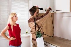 Männliche Arbeitskraft-Sprühschädlingsbekämpfungsmittel auf Regal in der Küche stockbilder