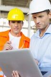 Männliche Architekten, die an Laptop an der Baustelle arbeiten Stockbilder