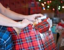 Männliche Arme und die Hände, die Weihnachtsgeschenk mit undeutlichem Baum öffnen, beleuchtet im Hintergrund stockfotografie