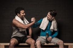 Männliche Athleten, die am Turnhallenumkleideraum stillstehen und sich unterhalten lizenzfreie stockbilder