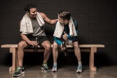 Männliche Athleten, die am Turnhallenumkleideraum stillstehen und sich unterhalten stockfoto