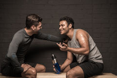 Männliche Athleten, die am Turnhallenumkleideraum stillstehen und sich unterhalten stockfotografie