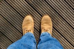 Männliche Beine mit Jeans und Stiefel, die auf hölzernen Planken stehen Lizenzfreies Stockbild