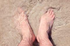 Männliche bloße Füße in einem warmen Sand auf einem sonnigen Strand während der Ferien stockbilder