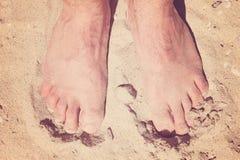 Männliche bloße Füße in einem warmen Sand auf einem sonnigen Strand während der Ferien Lizenzfreies Stockfoto