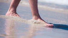 Männliche bloße Füße in einem warmen Sand, Mann, der einen Spaziergang auf einem sonnigen Strand mit Türkiswasser macht Lizenzfreies Stockbild