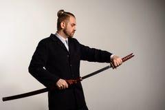 Männliche businessmanpulls heraus eine Klinge von japanischen Samurais stockfoto