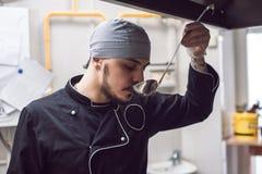 Männliche Chefprobierenmahlzeit in der Restaurantküche Lizenzfreie Stockfotos