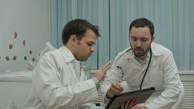 Männliche Doktoren, die auf Tabletten-PC aufpassen und Ergebnisse besprechen Stockfoto
