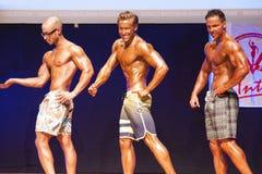 Männliche Eignungsmodelle zeigen ihre Konstitution in Badeanzug-OM-Stadium Stockbild