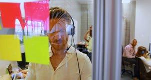 Männliche Exekutive, die auf Kopfhörer beim Schauen der klebrigen Anmerkung 4k spricht stock footage