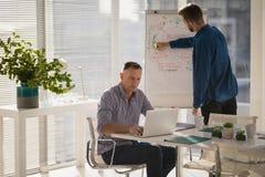 Männliche Exekutive, die Laptop während Mitarbeiterschreiben auf Flip-Chart verwendet stockfotos