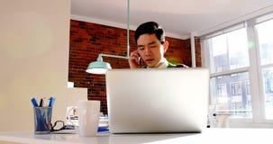 Männliche Exekutivunterhaltung am Handy bei der Anwendung des Laptops stock footage