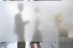 Männliche Exekutivunterhaltung mit weiblichem Kollegen hinter lichtdurchlässigem Wa lizenzfreie stockbilder