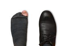 Männliche Füße in einem Schuh und in heftigen Socken lokalisiert auf weißem Hintergrund Stockfotografie