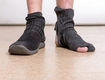 Männliche Füße mit Socke im Loch lizenzfreie stockfotos