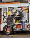 Männliche Feuerwehrmänner, die am LKW arbeiten Lizenzfreie Stockfotografie