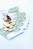 Männliche Figürchen, die auf Stapel Euromünzen und Banknoten sitzt Stockbild