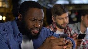 Männliche Freunde in der Kneipe unter Verwendung der Datierung von App auf dem Smartphone, Frauenprofile wählend stock video footage