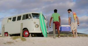 Männliche Freunde, die kühleren Kasten auf dem Strand 4k tragen stock footage
