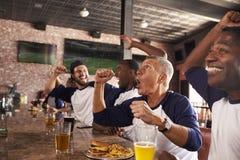 Männliche Freunde im Sportbar-Uhr-Spiel und feiern stockbild