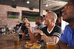 Männliche Freunde am Zähler in Sportbar-aufpassendem Spiel lizenzfreie stockfotos