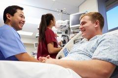 Männliche geduldige Unterhaltung mit medizinischem Personal in der Unfallstation Lizenzfreies Stockfoto