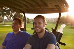Männliche Golfspieler, die Buggy entlang Fahrrinne des Golfplatzes fahren Stockbilder