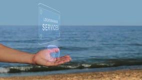Männliche Hände auf dem Strand halten ein Begriffshologramm mit den Standort-ansässigen Dienstleistungen des Textes stock video footage